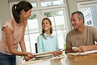Girl (7-9) helping parents set dining table, smiling
