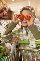Mother shopping with son (8-10) holding tomatoes up to eyes, smiling