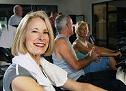 Senior woman on exercise machine in gym, smiling, portrait, close-up