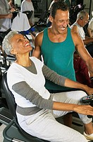 Male instructor with senior woman on exercise machine in gym, smiling