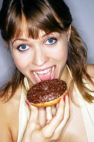Woman about to bite on a doughnut.