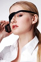 Businesswoman with eye patch talking on the cellphone
