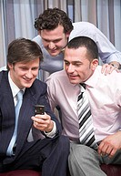 group of three businessmen looking at display of mobile phone