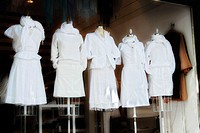 Women's white summer clothing displayed in a retail store window