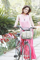 Portrait of a young woman with a bicycle in the garden