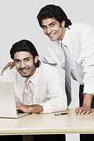 Portrait of two businessmen in front of a laptop
