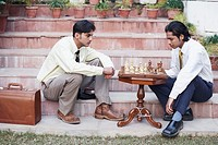 Side profile of two businessmen playing chess