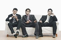 Three businessmen sitting on a couch holding mobile phones