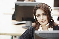 Portrait of a businesswoman wearing a headset sitting in front of a computer