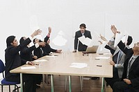 Group of business executives throwing sheets of paper in a meeting