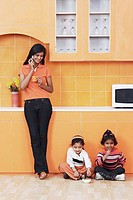 Mother talking on a mobile phone with her daughters sitting on the floor