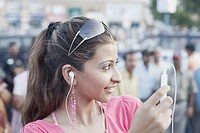 Close-up of a young woman listening to an MP3 player (thumbnail)