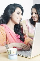 Mid adult woman using a laptop with a young woman beside her