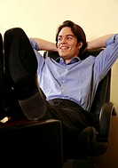 Young businessman relaxing with hands behind head (thumbnail)