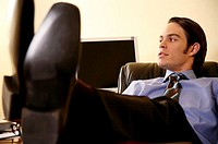 Young businessman sitting with feet on desk (thumbnail)
