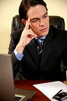 Young businessman sitting at desk and thinking (thumbnail)
