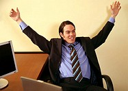 Young businessman smiling and raising arms in excitement