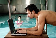 Man on computer nex t to a swimming pool
