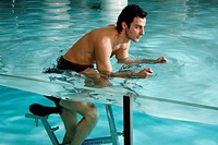 Young man on exercise bike in spa pool