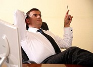 Businessman sitting at his desk with hands behind his head