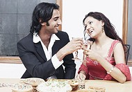 Young couple toasting with wineglass at the dining table