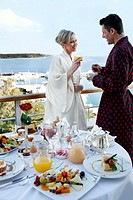 Mature couple having breakfast on hotel terrace (thumbnail)