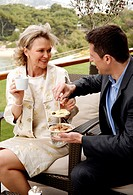 Mature couple having beverages on hotel terrace