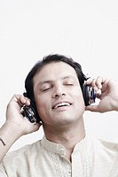 Close-up of a mid adult man wearing headphones listening to music