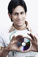 Portrait of a young man holding a CD