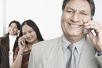 Close-up of a businessman talking on a mobile with two mature women standing behind him