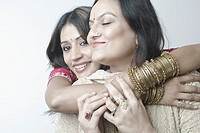 Close-up of a mid adult woman hugging a mature woman