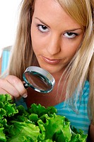 Woman viewing vegetables with a magnifying glass