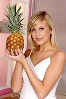 Woman holding a pineapple.