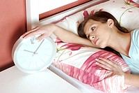 Woman checking the time on the alarm clock