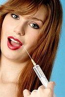 Woman injecting her lips with a syringe