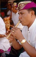 A Balinese musician plays a flute. Ubud. Bali. Indonesia.