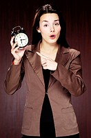 Businesswoman pointing at the alarm clock