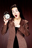 Businesswoman pointing at an alarm clock