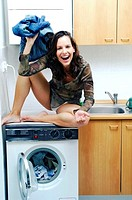 Woman sitting on the washing machine