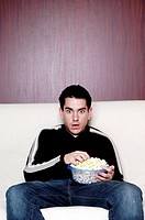Man eating popcorn while watching movie.