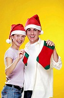 Couple in christmas hats holding christmas socks.