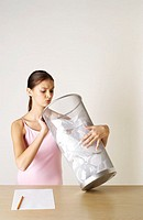 Girl looking into a dustbin of crumpled papers (thumbnail)