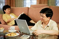 Man using the laptop while his wife reading book in the living room.