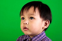 Studio shot of boy in checkered shirt on a green background.