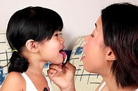 Woman watching her daughter licking the cream off her biscuit