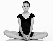 Woman in fitness wear sitting in a meditating position.