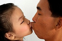 Father and daughter kissing.