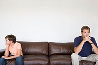 Father and son at opposite ends of sofa