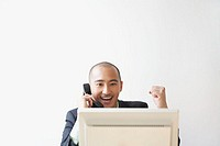 Businessman on telephone behind computer monitor