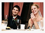 Bride and groom at dinner table clapping